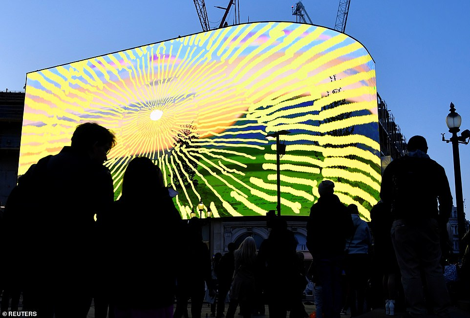 Londoners have gathered at Piccadilly Circus (pictured) to view David Hockney's new video artwork made on his iPad which features an animated sunrise