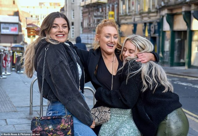 Three girls hug each other, with one clutching a drink, as they enjoy their night out in Newcastle city centre