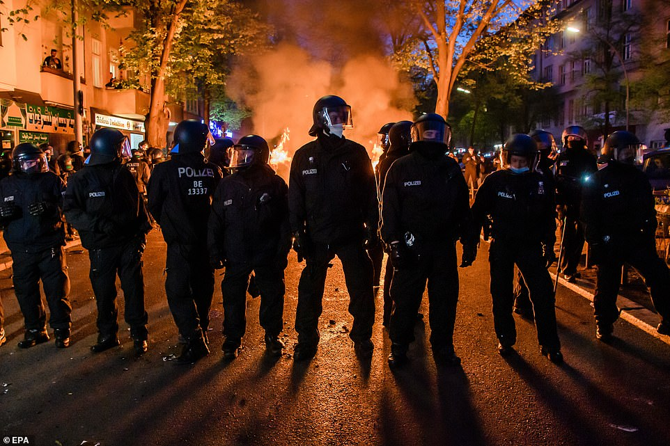 BERLIN, GERMANY: Riot police take up a position in a street in the German capital tonight in front of a burning barricade