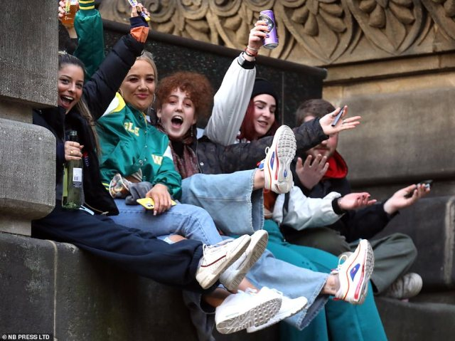 A ground of friends are seen sitting on a stone wall smiling and having a good time in Leeds on Saturday night
