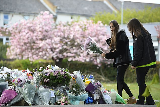 Two women lay flowers in a park in Aylesham village yesterday close to the scene where PSCO Julia James was found