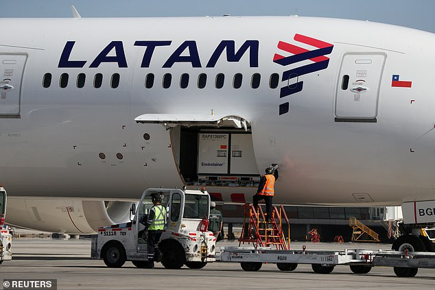 Workers unload containers transporting a batch of the Sinovac coronavirus vaccine at the international airport of Santiago, Chile