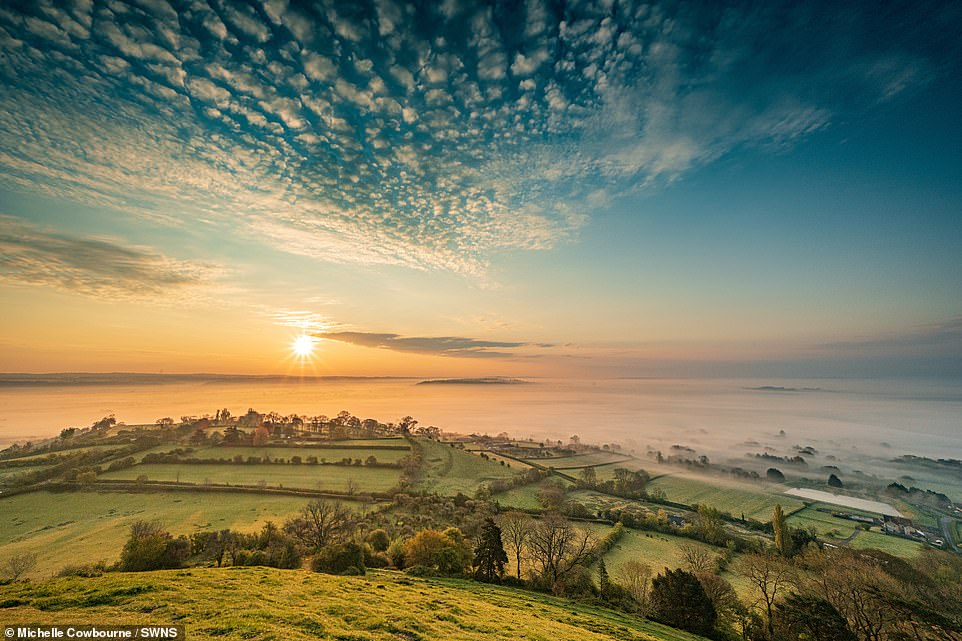 Pictured: An almost cloudless sunrise on a cold and misty morning in Glastonbury Tor, Somerset