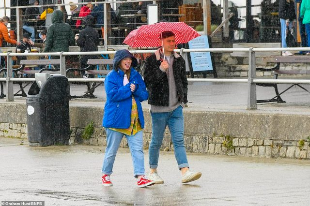 Visitors to Lyme Regis hold umbrellas as they flock to the beach