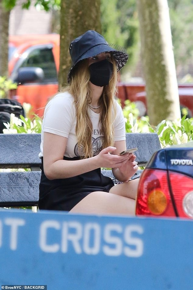 Taking it easy: Lawrence glanced through her phone on the park bench