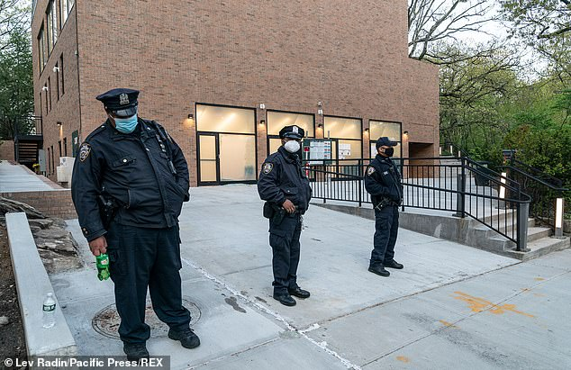 Police stand guard in front of one of the Jewish-related buildings in the Bronx as the NYPD's Hate Crime Task Force is investigated the incidents