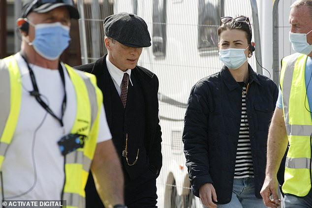 Peaky Blinders cast and crew were told to continue filming after someone tested positive for Covid-19, insiders claim. Pictured: Cast and crew of Peaky Blinders wearing masks as they resume filming. There is no suggestion the pictured crew members tested positive