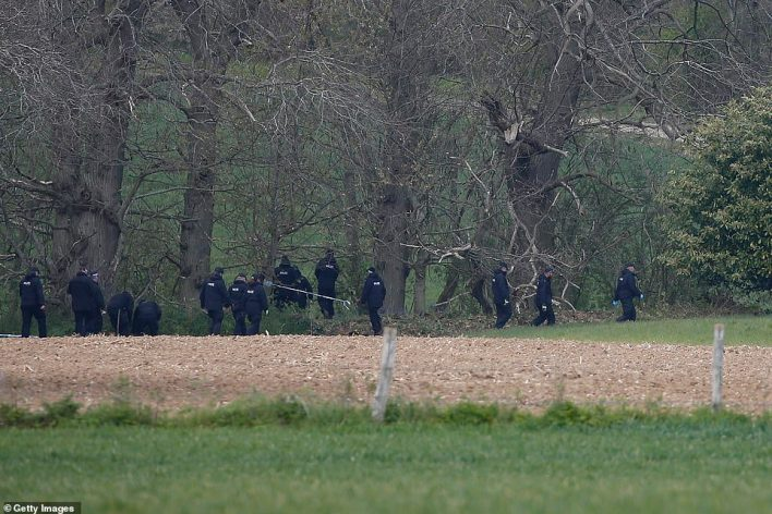 Police officers walk near Ackholt Wood on Sunday as they search for information surrounding the death