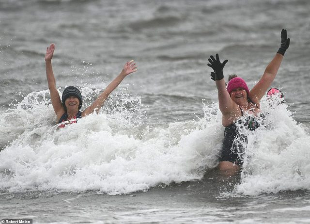 Swimmers brave the chilly sea at Langland Bay, Swansea on a wet and windy Bank Holiday Monday