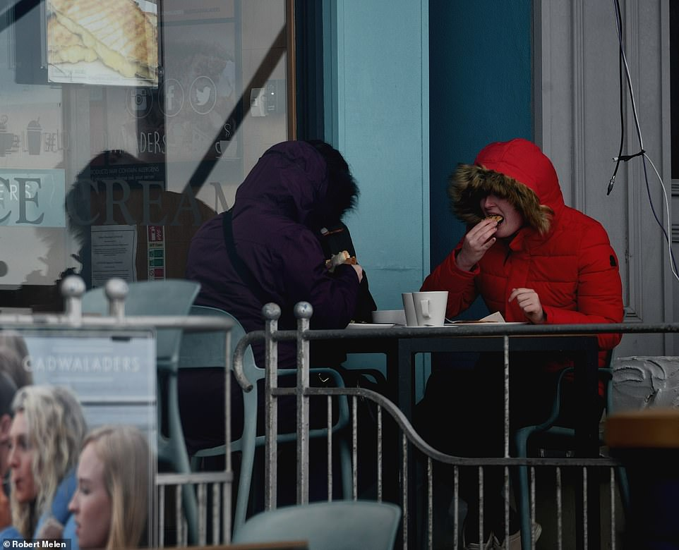 People sit down for lunch outside with hoods up on a wet and windy Bank Holiday Monday in Porthcawl, Wales