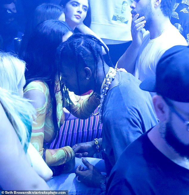 Packing on the PDA: Travis touched the stunner's hand as they had an intimate conversation in the packed nightclub