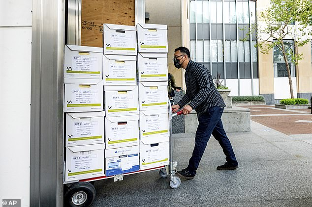 A member of Apple's legal team rolls exhibit boxes into the court on Monday ahead of opening statements in the antitrust trial