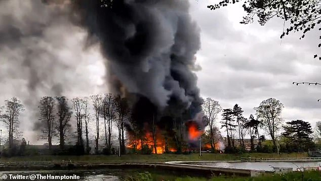 Witnesses reported hearing explosions after a fire engulfed an industrial unit on Platt's Eyot, an island on the River Thames, near Hampton, London, today
