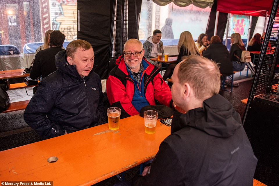 Pub-goers refused to let the wet weather dampen their spirits as they sad under awnings in Manchester city centre