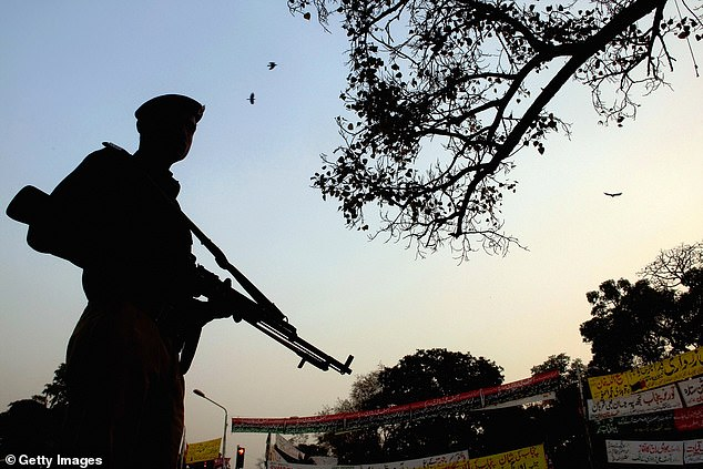 A British woman has been murdered by gunman at a rented home in Pakistan on Monday, it has been reported. Pictured: Police in Lahore stand guard outside a home [file photo]
