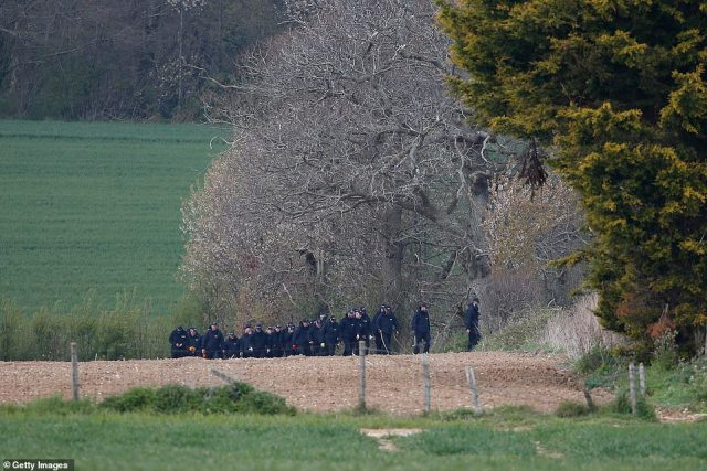 Scores of police officers conduct a search in a field next to Ackhold Wood on Sunday as the hunt for her killer continued