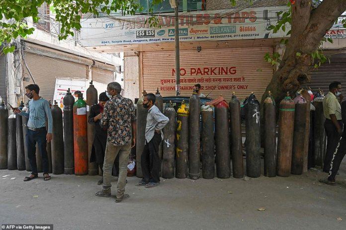 La gente espera para volver a llenar sus cilindros de oxígeno médico en una instalación privada en Delhi el martes