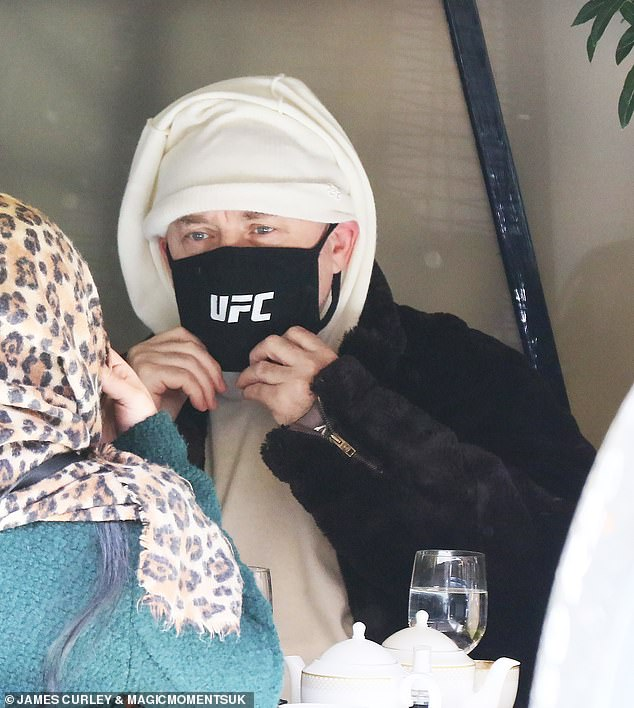 UFC me?  He went for a funky style statement in a face mask featuring the Ultimate Fighting Champion logo and a brown fur coat.