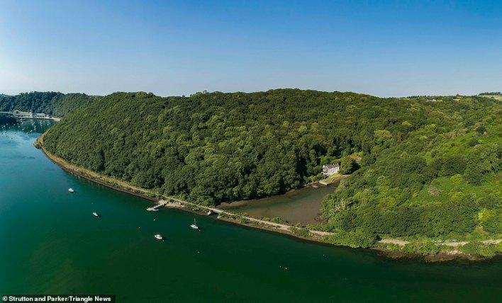The entrance to the main house has a spacioius conservatory with a slate floor and wonderful views of the water and woodland. The house is only accessible via foot or by boat andis surrounded by over 32 acres of private woodland and with its own mooring on the Fowey Estuary