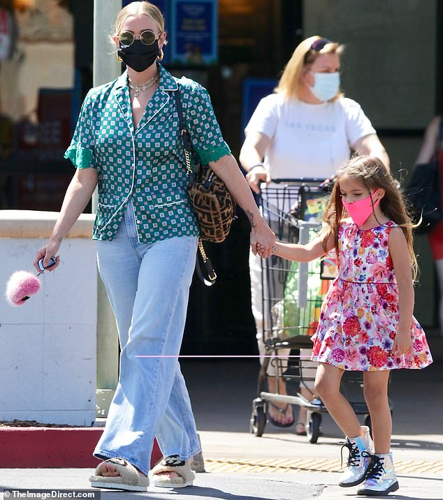 Shopping: The pop act held her baby girl's hand as they exited the grocery store and headed to the parking lot together