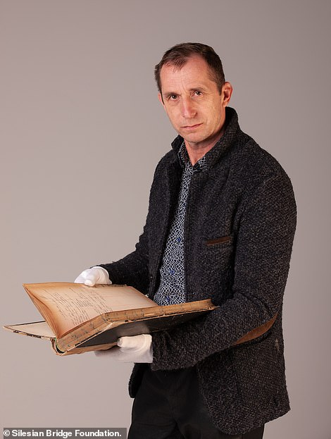 Roman Furmaniak, head of the Silesian Bridge foundation leading the hunt for the treasure, holding the diary