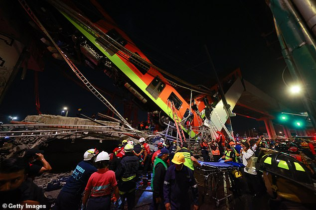 Rescue workers make their way on to the train to help the wounded after two trains collapsed from an overpass track