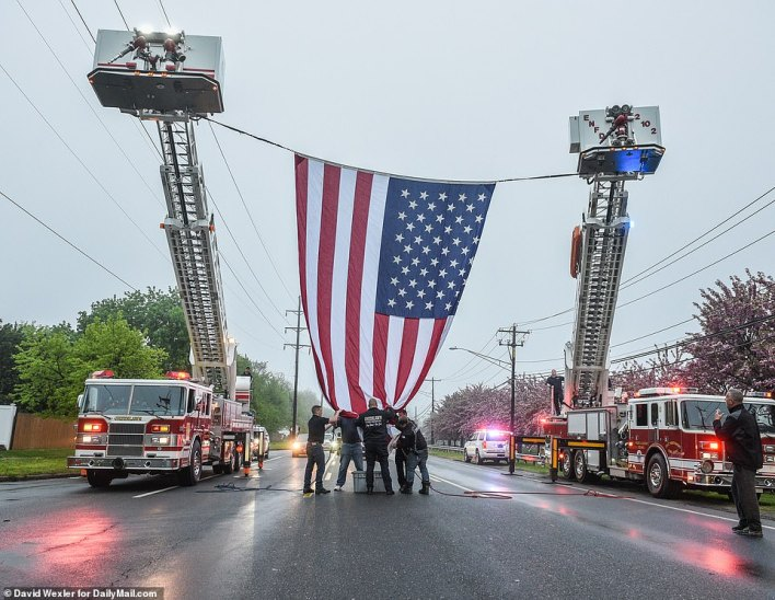 A huge American flag is raised for the funeral one week after he died while redirecting traffic on the LIE