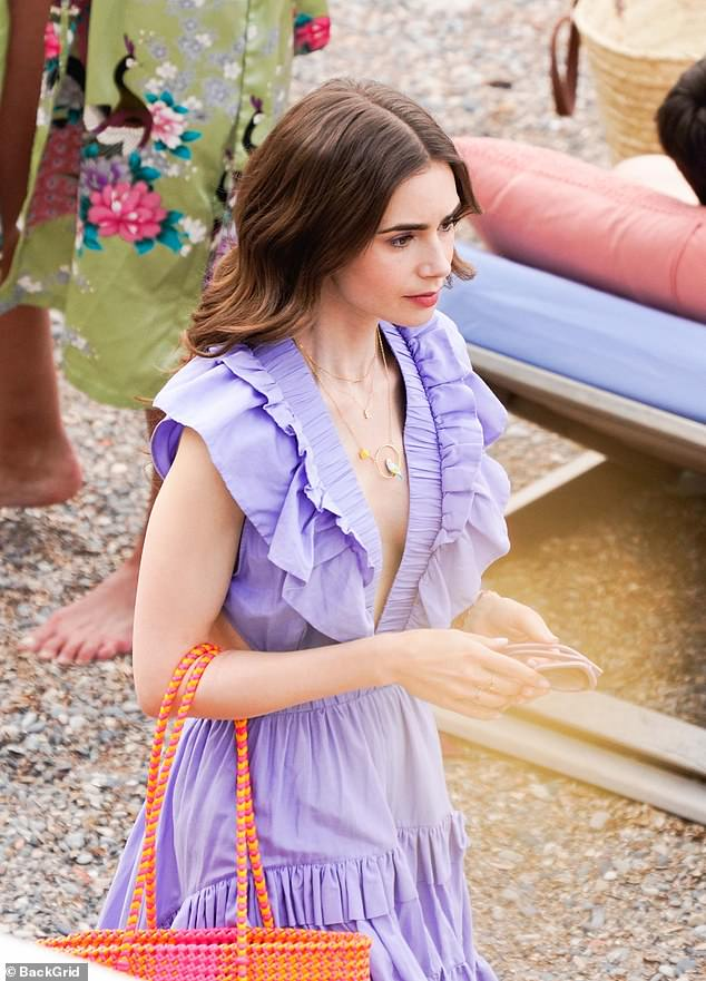 Details: She styled her pretty dress with a selection of necklaces including a delicate gold E