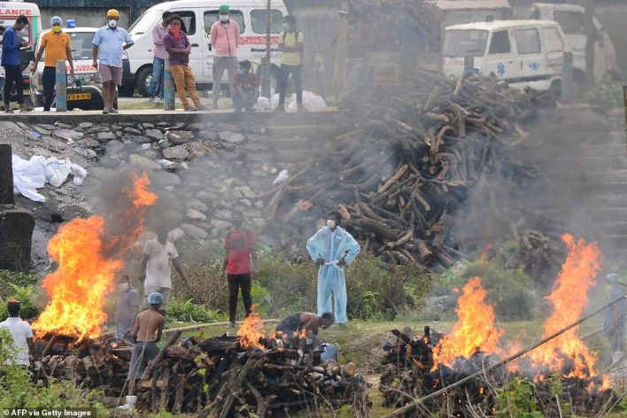 People watch the cremation of people who died due to the Covid-19 coronavirus at Sahudangi Crematorium, some 15 Km from Siliguri on May 4, 2021