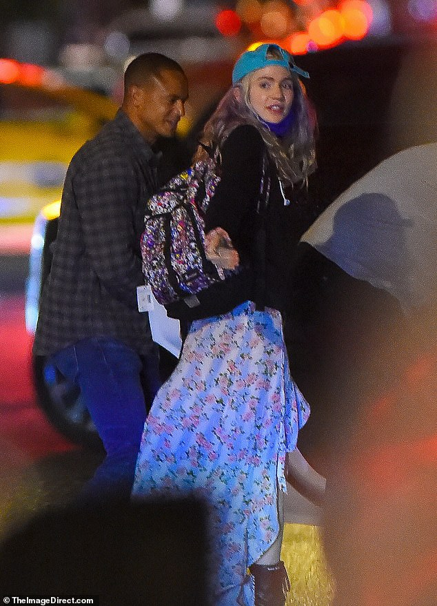 On the move: Grimes, carried a floral backpack, no doubt containing some travel essentials for their tot