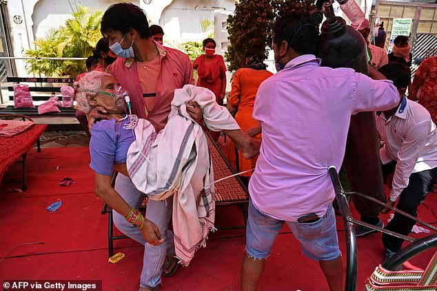 A family member carries a patient breathing with the help of oxygen under a tent installed along the roadside