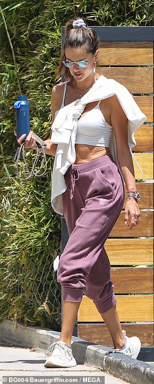 Essentials: As she stepped out of the Pilates studio with Delfino by her side, Alessandra could be seen carrying a reusable blue water bottle and her cell phone in one hand