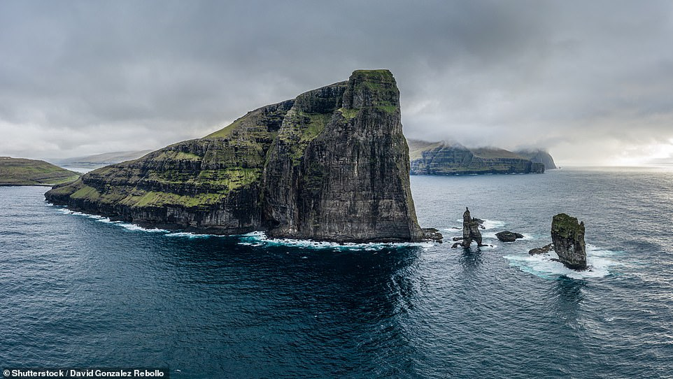 The Faroe Islands' Risin og Kellingin, or The Giant and the Witch, sea stacks (seen to the right) attract thousands of sightseers every year. The rock formations are best seenfrom either the village of Tjornuvík on Streymoy island or halfway between the village of Eidi and the Eidisskard mountain pass on Eysturoy island. In terms of stature, Risin stands 233ft- (71m) high while Kellingin is 226ft (69m) above sea level. The sheer cliff that towers over them to the left is called Eidiskollur, which is1,155ft (352m) tall