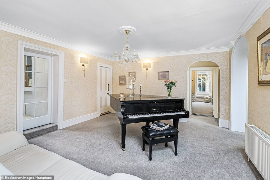 The home even has space for a grand piano and has been fitted with light grey carpets and patterned wallpaper
