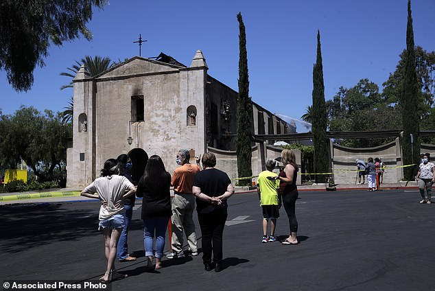 Onlookers stand outside the San Gabriel Mission in the aftermath of a morning fire, Saturday, July 11, 2020, in San Gabriel, California.More than 85 firefighters, 12 engine companies, five truck companies, four rescue ambulances and five battalion chiefs were called to the blaze, according to the San Gabriel Fire Department