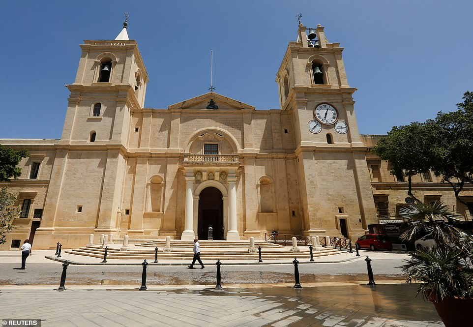 People walk outside St John's Co-Cathedral in Valletta, as Malta may be one of the countries added to the 'green list' today