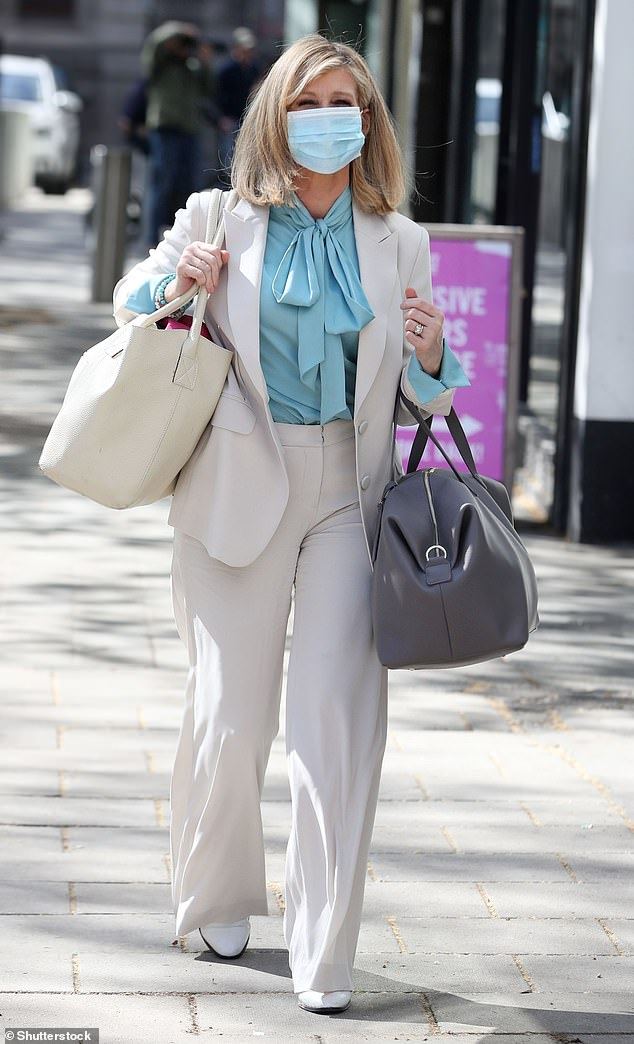Stylish: Under the double-breasted blazer, she wore a baby blue shirt that was tied in a knot at the neck