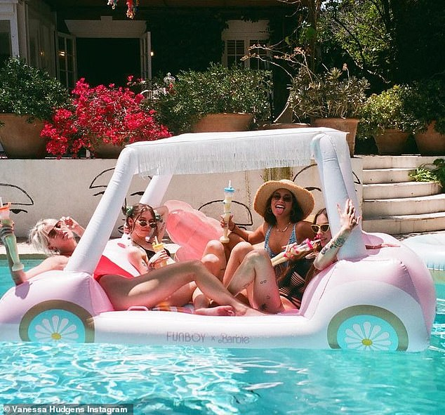 Summer fun: 'Real hot girl summer,' she wrote alongside another of her with the gang riding in an inflatable pool toy with their giant libations in hand.The Rent Live performer has also kept busy working on her new line of cactus water, Cali Water