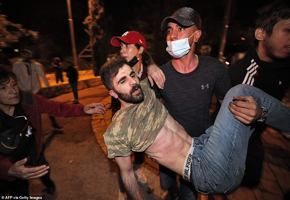 At least 178 Palestinians and six officers were injured in the night-time clashes at Islam's third-holiest site and around East Jerusalem, Palestinian medics and Israeli police said, as thousands faced off against several hundred Israeli police in riot gear. Pictured, an injured Palestinian protestor