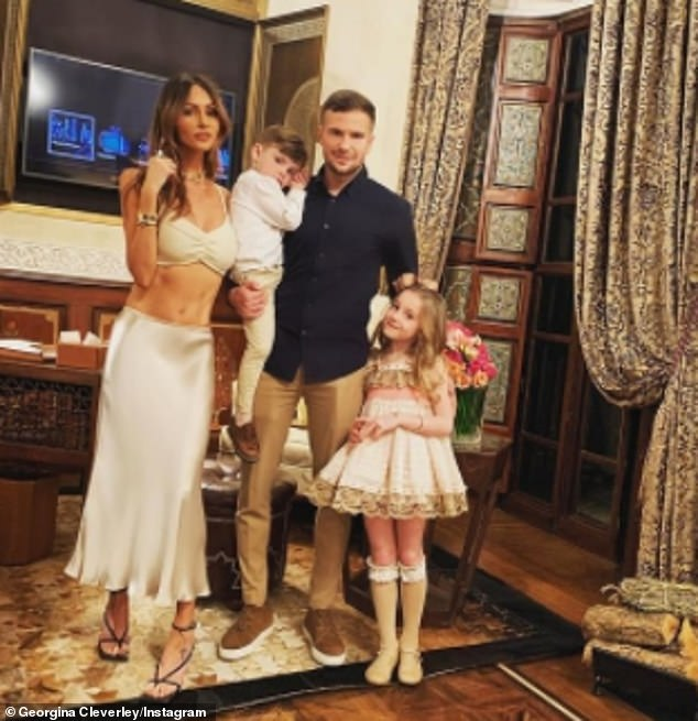 So sweet:In the photo, Georgina's husband Tom, 31, and their two other children - Albie and Nevaeh - put their hands on her growing tummy (pictured together in February 2020)