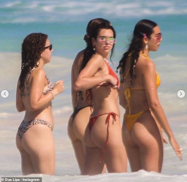 Svelte figure: In contrast, the Don't Start Now singing sensation appeared unimpressed in a photo on the beach as she went for a dip with her pals in a sizzling red bikini
