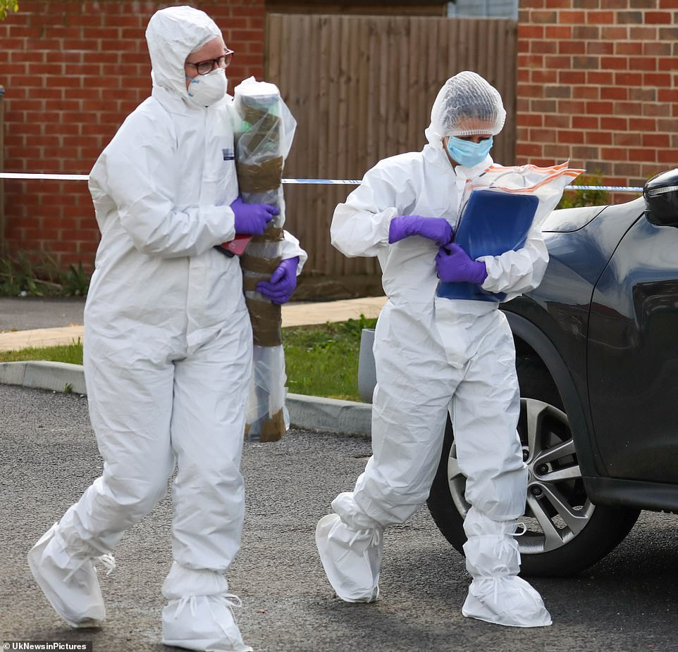 Two forensic police officers carry away materials from the house inAylesham, Kent as they continued their searches