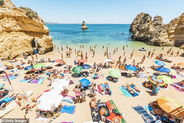 Portugal, Gibraltar and Israel are among the small group of countries which will be on the green list from May 17 - with some countries on the list still not accepting holidaymakers. Pictured: Tourists sunbathing in Praia do Camilo, Lagos, Faro district, Algarve, Portugal