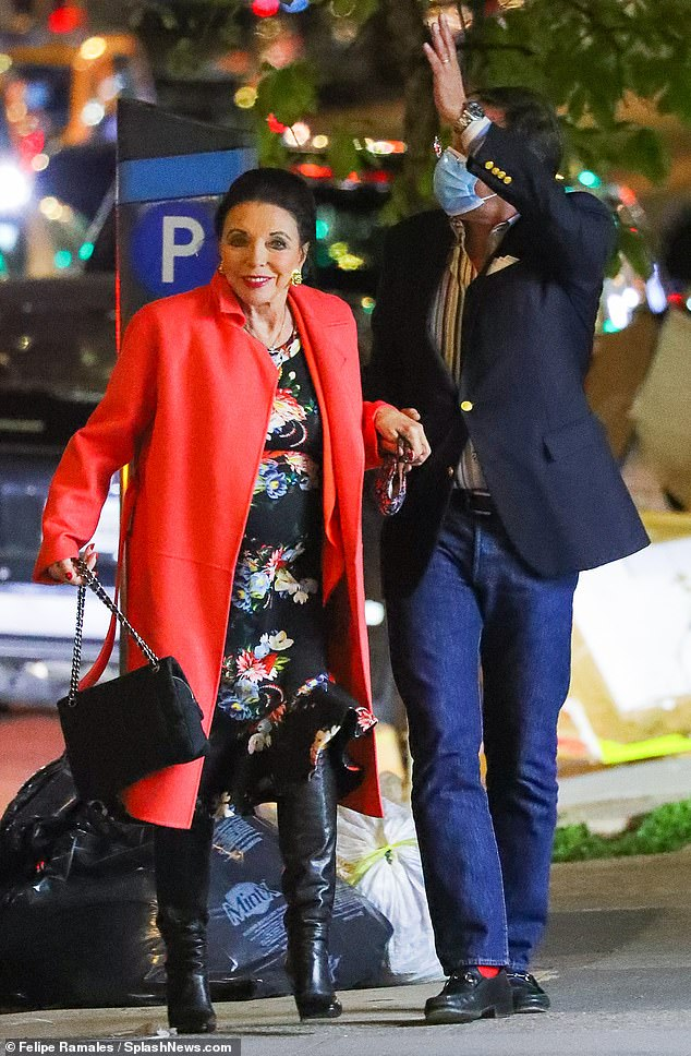Late date: Joan wore a scarlet coat over a floral print dress and long black boots, while Percy opted for a chic casual outfit in jeans, a white shirt and a navy blazer