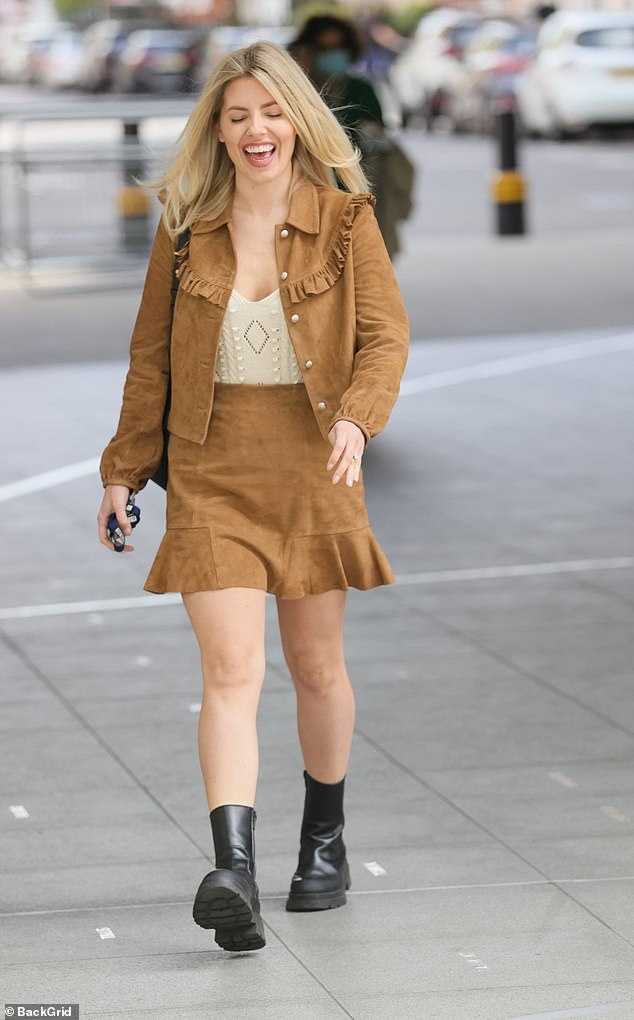 Happy girl: Mollie beamed as she headed for work in the cute matching outfit that featured shiny gold buttons and a chic ruffle detail