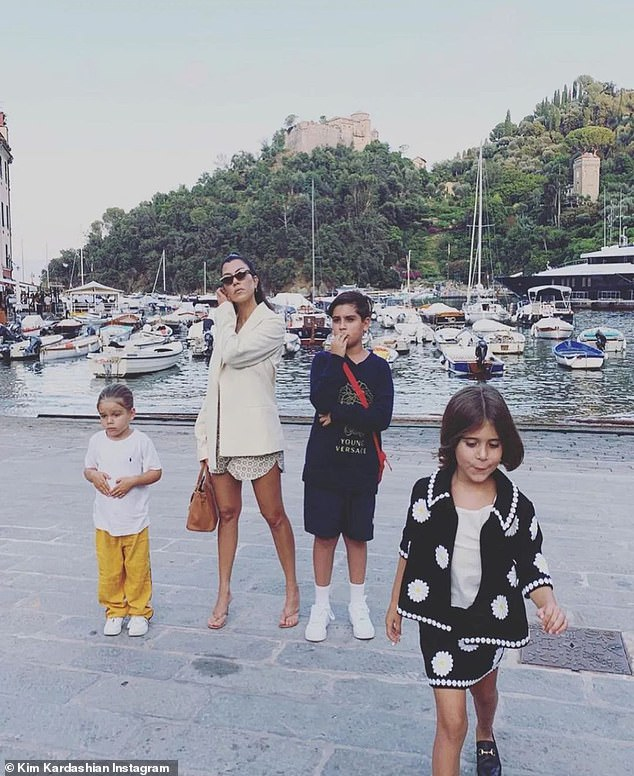 Family: Kim then added a vacation image of older sister Kourtney, 42, standing at a European dock with her three kids: Mason, 11, Penelope, eight, and Reign, six