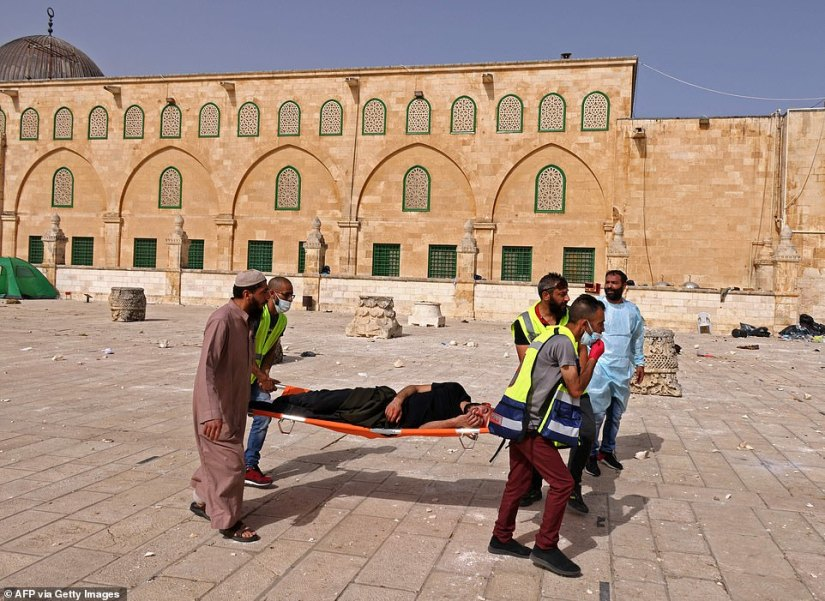 Palestinian medics evacuate a wounded protester amid clashes with Israeli security forces at Jerusalem's Al-Aqsa mosque compound