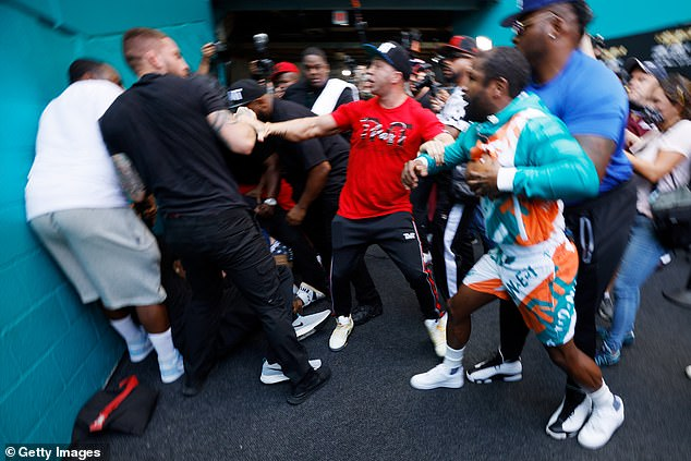 Mayweather had to be held back by security while Paul was quickly pinned down to the floor