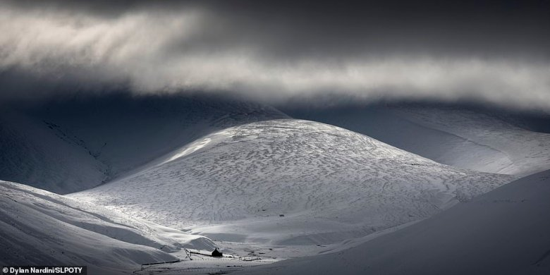 Another incredible shot from Nardini's portfolio. He snapped it after snowfall in February 2020 in the village of Leadhills in the Southern Uplands in South Lanarkshire.He said: 'The village had been lacking in light until a sudden brief thinning of the thick flat cloud allowed small piercing beams to pepper the textured snow-covered hills of the Southern Uplands and the deserted old shepherd's bothy nestled at their foot'