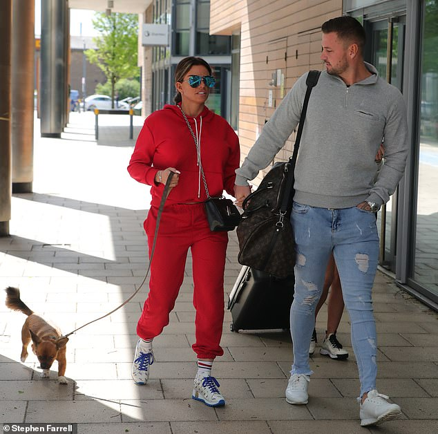 In good company:Katie and Carl, who at 32 is 10-years her junior, were joined by their pet dog Sid as they made their way into the building after travelling north from their Sussex home